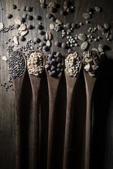 Cuillères en bois avec des céréales et des graines sur bois