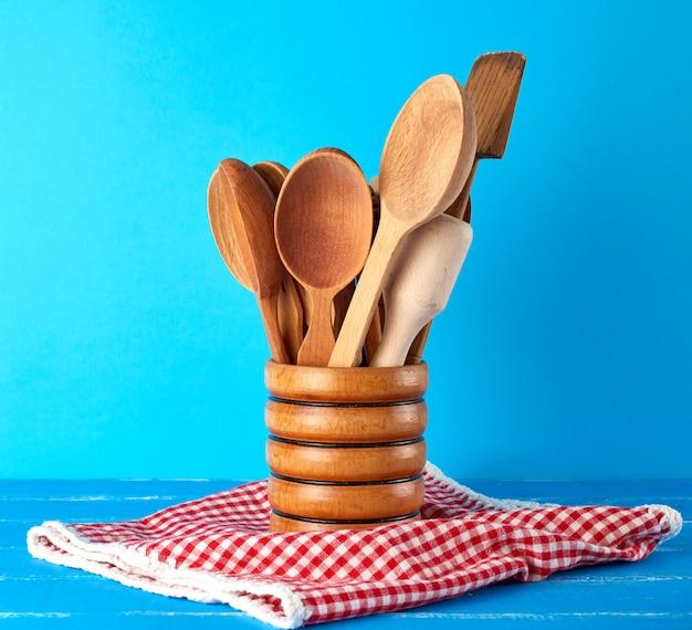 Cuillères en bois dans un récipient en bois sur une table bleue