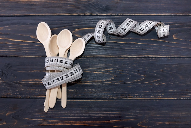 Cuillères en bois entrelacées avec un ruban à mesurer sur une surface en bois.