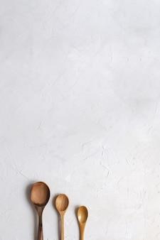 Cuillères en bois sur fond blanc en béton.