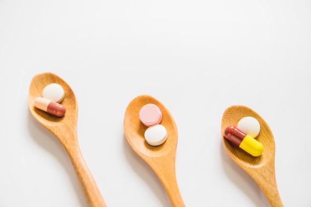 Cuillères en bois obliques avec des pilules sur fond blanc