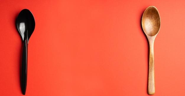 Cuillères en bois et en plastique sur fond rouge. couverts en plastique, écologie, pollution de l'environnement par le plastique, vaisselle jetable, concept de recyclage des déchets. copyspace, mise à plat.zéro déchet