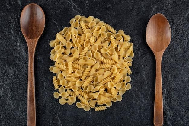 Cuillères en bois pleines de macaroni farfalle tonde cru.