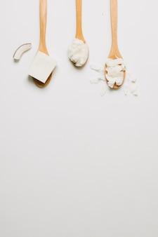 Cuillères en bois avec des produits de noix de coco et copie-espace