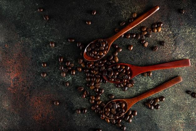 Cuillères en bois remplies de grains de café kopi luwak dans l'obscurité