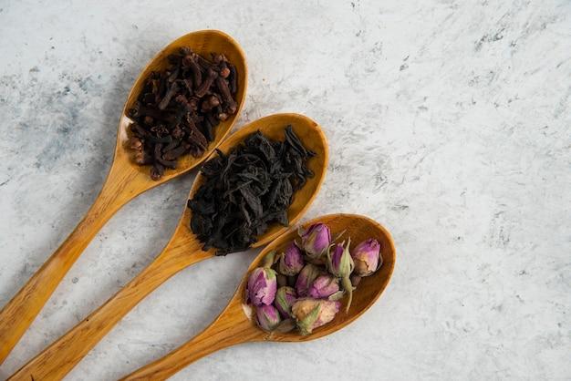 Cuillères en bois avec roses séchées, thés en vrac et clous de girofle.