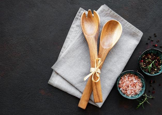Cuillères en bois, serviette et épices sur une surface noire