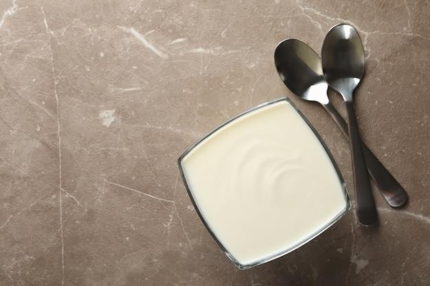 Cuillères et bol de crème sure sur fond gris, vue du dessus
