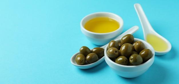 Cuillères et bols aux olives et huile sur bleu