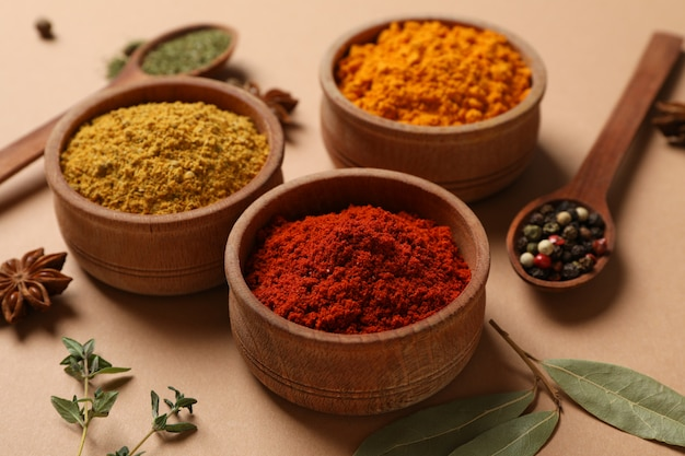 Cuillères et bols avec différentes épices en poudre sur fond d'artisanat, close up