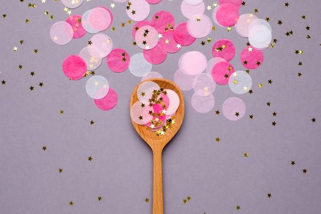 Cuillères et confettis roses sur gris