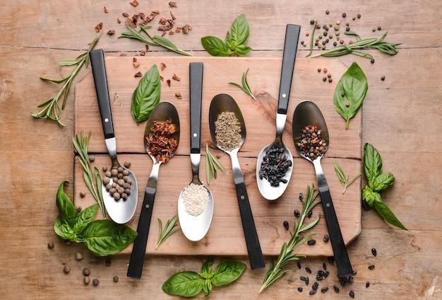 Cuillères avec différentes épices sur bois