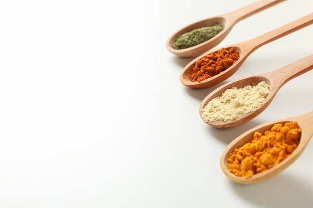 Cuillères avec différentes épices en poudre sur fond blanc, espace pour le texte