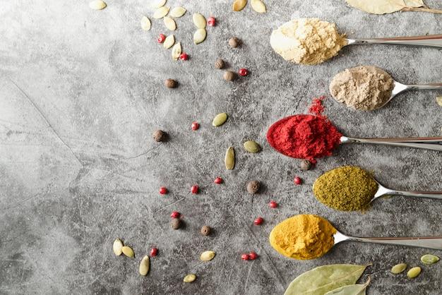 Cuillères avec diverses poudres de condiments et graines