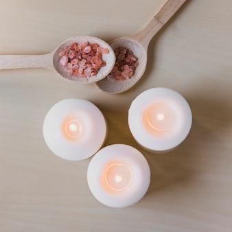 Cuillères avec du sel aromatique près des bougies