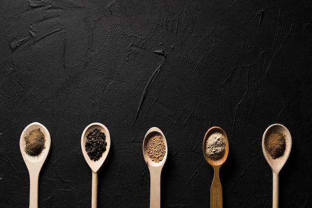 Cuillères avec des épices sur noir