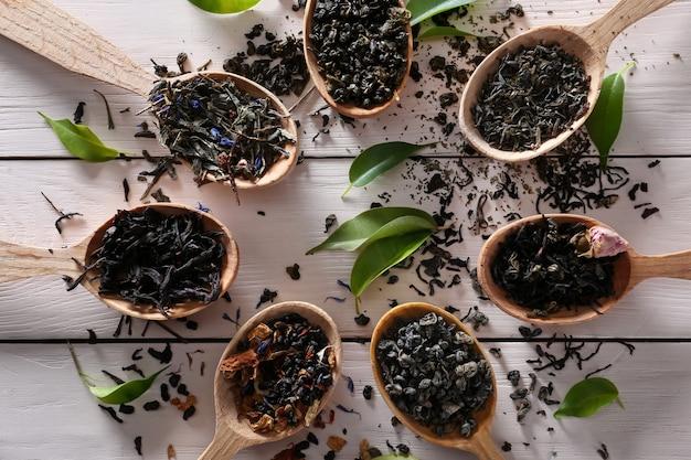 Cuillères avec des feuilles de thé séchées sur table en bois blanc