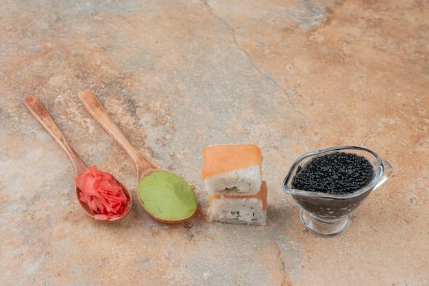 Cuillères de gingembre et vasabi avec deux sushis et caviar sur marbre.