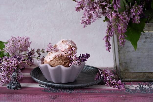 Cuillères à glace au chocolat dans une tasse en céramique sur un plateau en bois et des branches de lilas