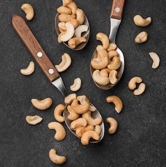 Cuillères de gros plan remplies de noix de cajou crues saines