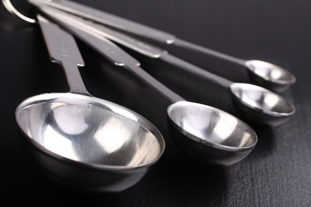 Cuillères à mesurer en métal vide sur fond noir