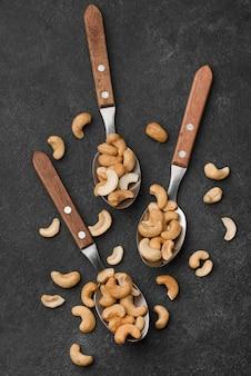 Cuillères avec des noix de cajou crues saines