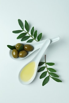 Cuillères avec olives et huile, et brindilles sur blanc