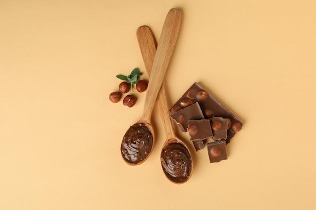 Cuillères à pâte de chocolat, noix, chocolat et menthe sur fond beige