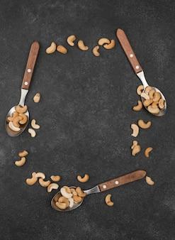 Cuillères remplies de noix de cajou crues saines copy space