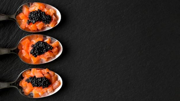 Cuillères vue de dessus avec caviar et poisson