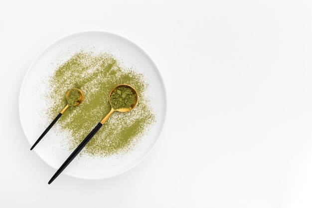 Cuillères vue de dessus avec poudre de matcha sur une assiette