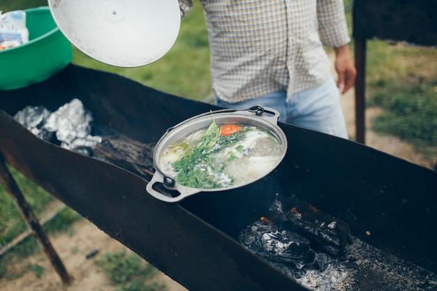 Cuire des aliments dans un camping ou un centre de loisirs, soupe de poisson cuite sur le gril