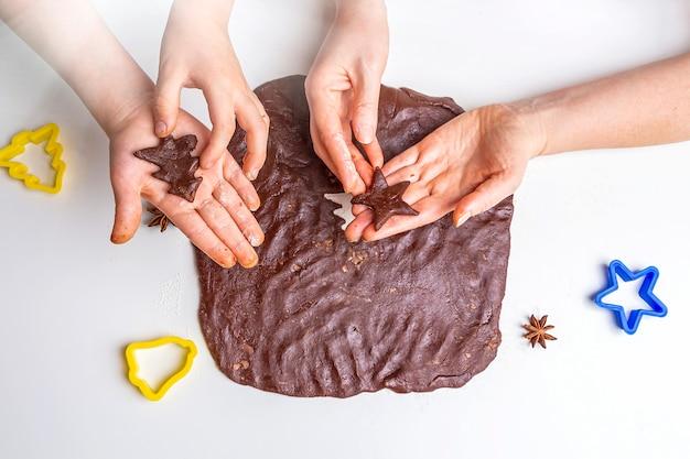 Cuire des biscuits au chocolat de noël et du nouvel an ou du pain d'épice. cuisson festive traditionnelle, cuisiner avec les enfants. étape 11 découpez la pâte roulée avec des moules. recette étape par étape