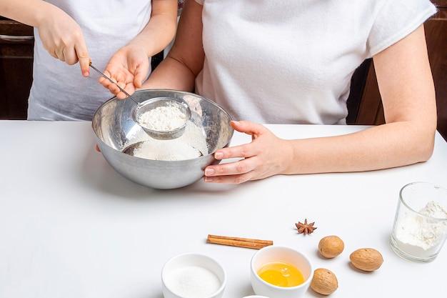 Cuire des biscuits au chocolat de noël et du nouvel an ou du pain d'épice. cuisson festive traditionnelle, cuisiner avec les enfants. étape 2 passer la farine au tamis. recette étape par étape.