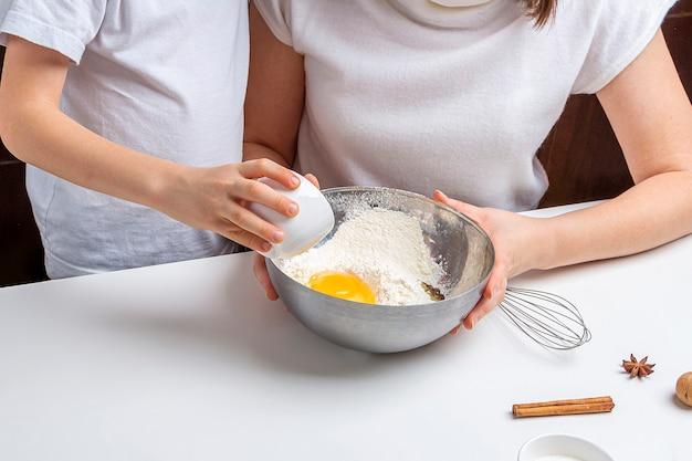 Cuire des biscuits au chocolat de noël et du nouvel an ou du pain d'épice. cuisson festive traditionnelle, cuisiner avec les enfants. étape 4, ajoutez un œuf dans le bol. recette étape par étape.