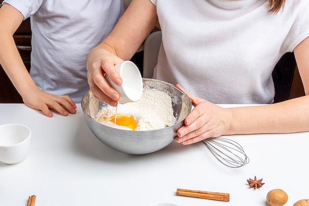 Cuire des biscuits au chocolat de noël et du nouvel an ou du pain d'épice. cuisson festive traditionnelle, cuisiner avec les enfants. étape 5 versez le lait dans le bol. recette étape par étape.