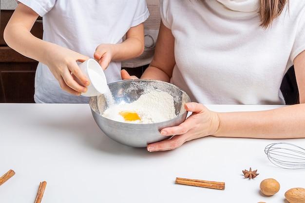 Cuire des biscuits au chocolat de noël et du nouvel an ou du pain d'épice. cuisson festive traditionnelle, cuisiner avec les enfants. étape 6, ajoutez le sucre dans le bol. recette étape par étape.