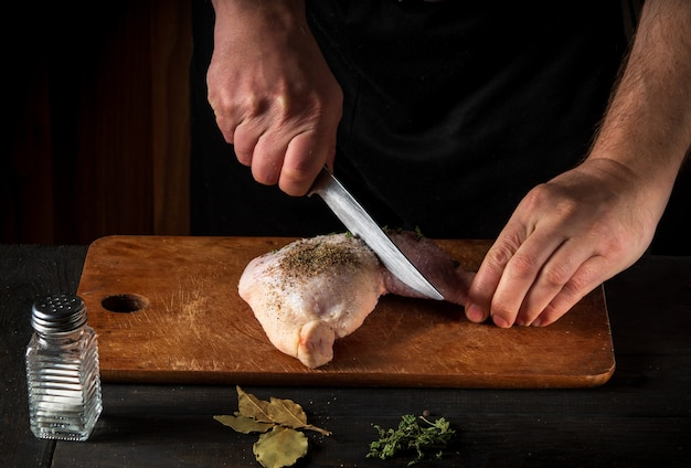 Cuire une cuisse de poulet avec les mains d'un chef sur un fond sombre.