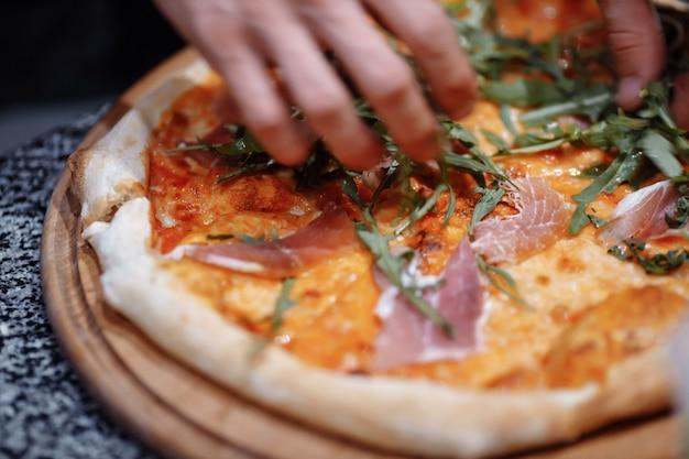 Cuire dans la cuisine en mettant les ingrédients sur la pizza. notion de pizza. production et livraison de nourriture.