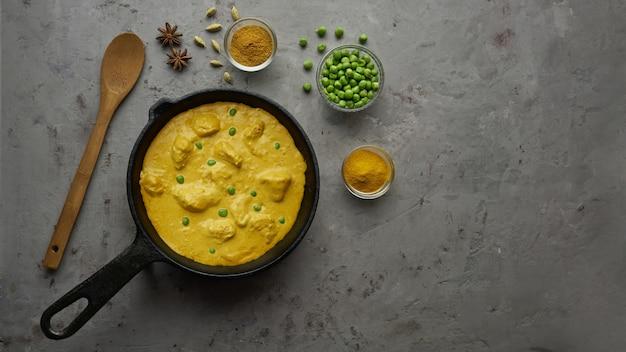 Cuire un délicieux poulet au curry dans une poêle avec des épices. mise à plat, vue de dessus avec espace de copie