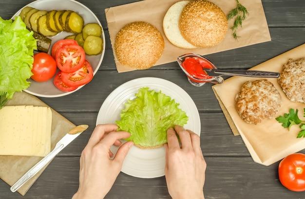 Cuire un hamburger étape par étape, étape 4 - mettre une laitue sur la sauce