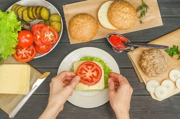 Cuire un hamburger étape par étape, étape 7 - mettre une tranche de tomate sur le fromage