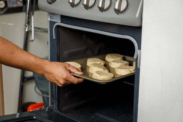Cuire à la maison mettre un plateau avec des biscuits au four de la cuisinière