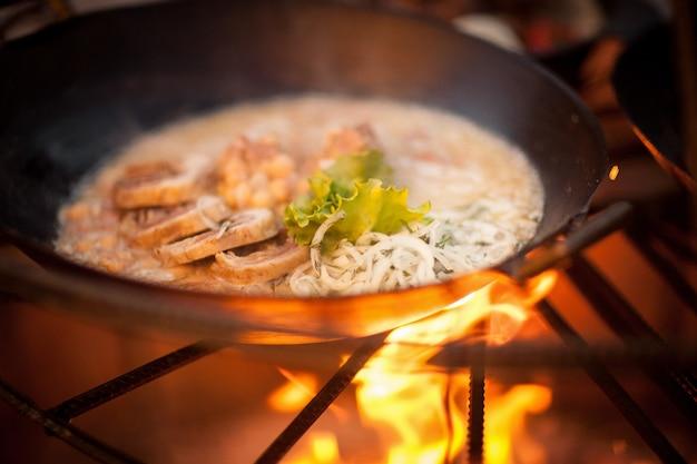 Cuire un plat de viande avec des petits pois au bûcher avec des branches d'épinette