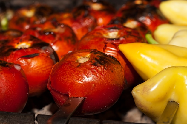 Cuire des poivrons et des tomates biologiques naturels sur des charbons, des légumes traditionnels pour les plats de viande