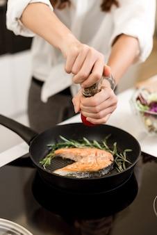 Cuire un steak de poisson avec des légumes et des épices sur une casserole dans la cuisine. alimentation saine et nutrition