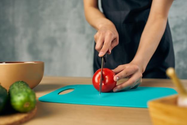 Cuire en tablier noir sur la planche à découper les légumes de la cuisine