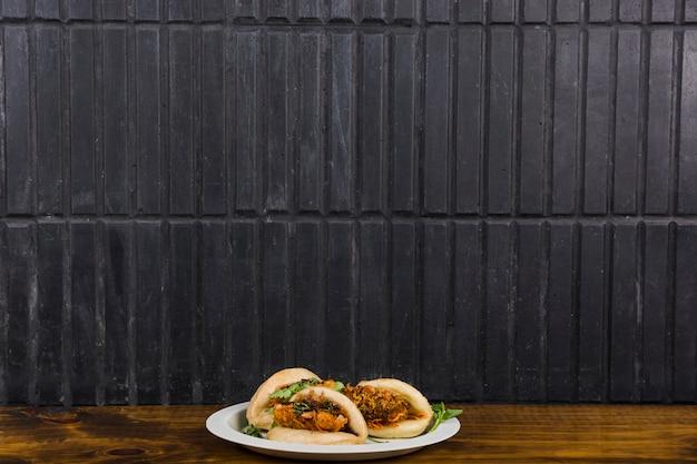 Cuisine asiatique gua bao à la vapeur de petits pains avec des légumes sur une table en bois contre le mur noir
