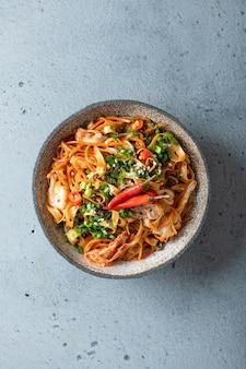 Cuisine asiatique, nouilles au wok et légumes dans un bol en céramique, vue du dessus
