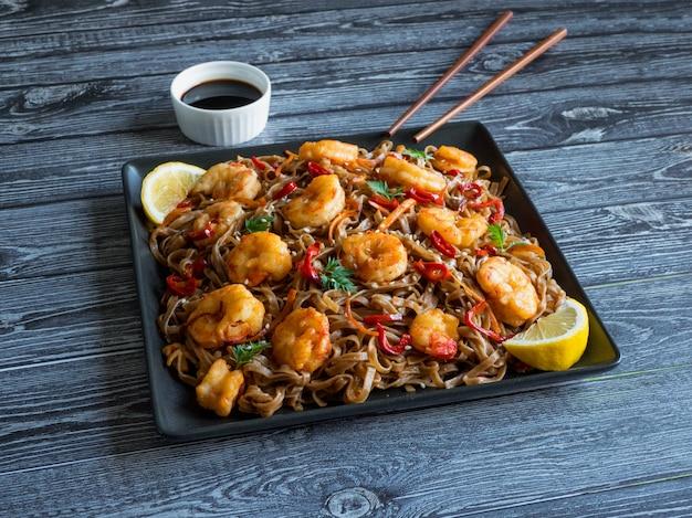 Cuisine asiatique nouilles udon aux crevettes frites, sésame et poivre gros plan sur une plaque sur la table en bois.